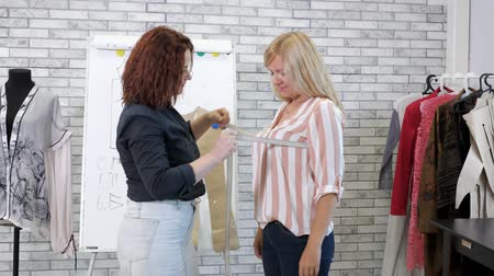 ruhakészítés : Dressmaker works in atelier. Seamstress takes measurements with tape of woman client in tailoring workshop. Individual tailoring to order. Sewing business.