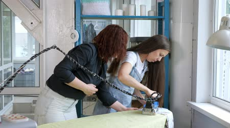 самодельный : Clothing manufacture. Seamstress is ironing clothes with iron, ironing with steam. She is teaching woman to iron costume. Small sewing business tailoring handmade clothes. Professional tailor at work.