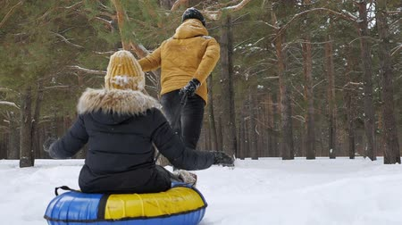 csőrendszer : Man is running and rolling woman on tubing by snow in winter forest, back view. Couple has a fun time in forest at weekend in slow motion.