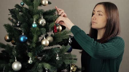 gevşemiş : happy young woman with loose hair in green sweater decorates artificial christmas tree with colorful toys close view Stok Video