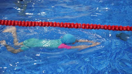 plazí : Child girl in goggles, swimsuit, cap and flippers is training swimming in pool. She swims in professional pool with transparent blue water. Child on swim lesson in sport school.