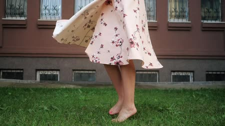 plavé vlasy : gorgeous lady with long loose fair hair in pink dress enjoys life and spins on green grass lawn close view slow motion close-up