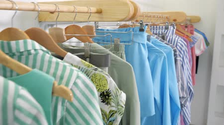 vállfa : camera motes along wooden hangers with fashionable colorful summer clothes on rack in modern designer shop close view