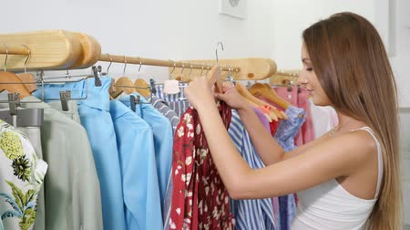 plavé vlasy : slim woman with loose fair hair holds wooden hanger and looks at blue summer dress near rack in shop close view