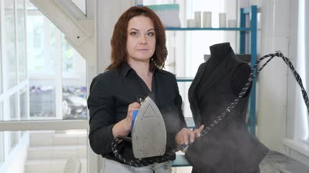 vest : Sewing products in tailoring business. Seamless woman with iron in hands looking at camera in tailoring workshop. Fashion designer at work steams clothes with iron. Stock Footage