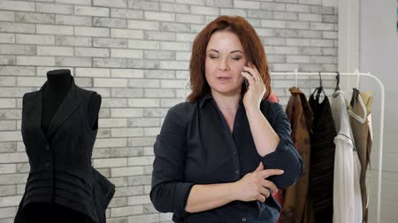 самодельный : Stylist is working in sewing factory workshop using mobile phone for job. Portrait of mature woman fashion designer talks with client on smartphone in clothing atelier. Clothing production business.