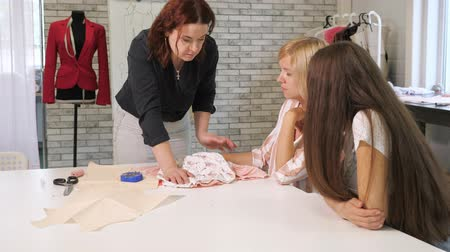 шитье дамского платья : Cutting and sewing courses. Seamstress teacher talks to students two woman about ways of processing tissue in workshop. Handmade tailoring and cutting clothes, needlewoman hobby. Sewing training.