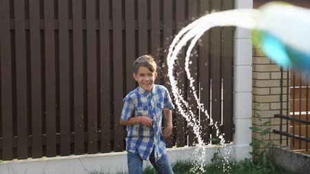 arma curta : cute short haired schoolboy in checkered shirt enjoys drops flowing from water gun on sunny day close view slow motion