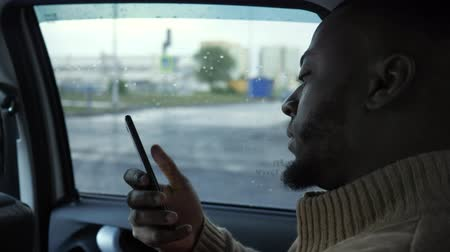 black cab : Portrait of black man is browsing smartphone. He is riding a car in rainy day in city. Afro american bearded guy is sitting in the back seat, side view.