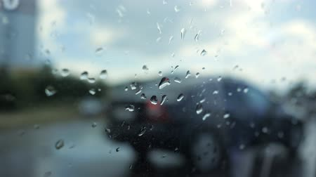 csöpögő : Raindrops on glass of window with cars and road outside, closeup. View from the car in the rain in city. Stock mozgókép