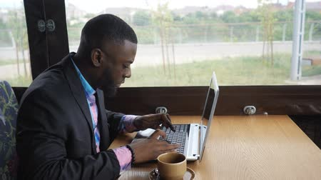 afro amerikai : Afro american businessman is typing a message on laptop sitting in summer cafe near window. Black man writes on computer, texting e-mail. He wears in shirt and suit jacket. Working with cup of coffee. Stock mozgókép