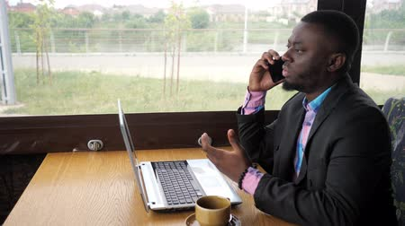 dark skinned : Afro american businessman working on laptop and talking mobile phone in cafe. He has a cup of coffee. Black man calling mobile phone and looking documents on computer. He wears shirt and suit jacket.