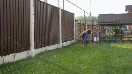 borrifador : happy little brothers enjoy life running along garden past lawn sprinkler against fence close low angle shot slow motion