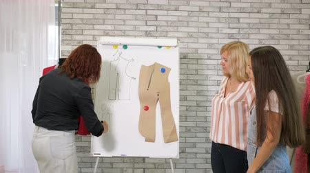 самодельный : Seamstress teacher explain creating pattern of jacket showing details on mannequin. Tailor teaches students to sew clothes on cutting and sewing courses in workshop. Cutting and sewing courses. Стоковые видеозаписи