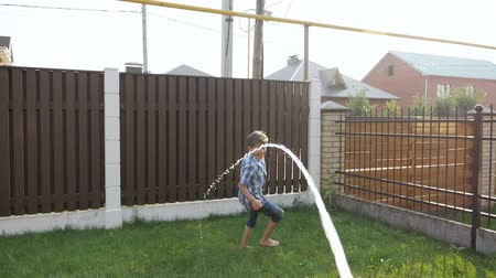 traumatic : happy boy in shorts runs away from water gun jet falls down on lawn and gets injured against fence closeup slow motion