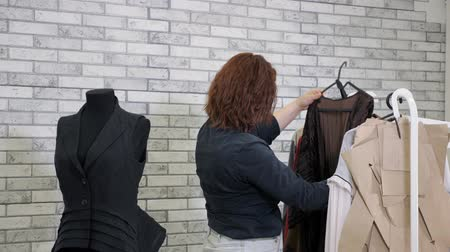 couturier : Working in tailoring business factory. Unrecognizable woman fashion designer in workshop chooses clothes hanging on hangers in atelier. She evaluates ready-to-run clothing models in production.