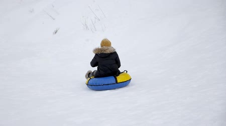 csőrendszer : Happy mom and son are sliding from snow hill at tubing in slow motion. Winter outdoor activity. Stock mozgókép