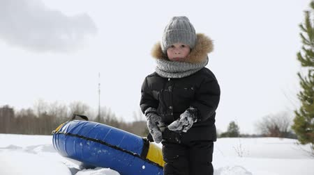 ruddy : Little boy in warm clothes and snowy mittens. He is walking pulling tubing for slide in snow in winter park. Winter fun on nature. Stock Footage