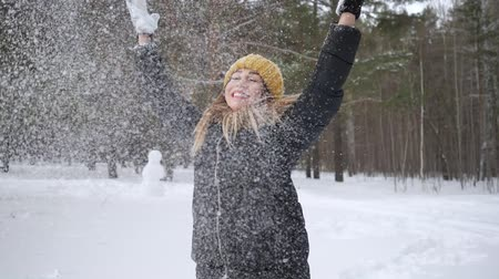 woodland : Happy smiling woman is throwing some snow in the air making a snowfall. She is enjoying the cold season in slow motion. Winter mood concept.