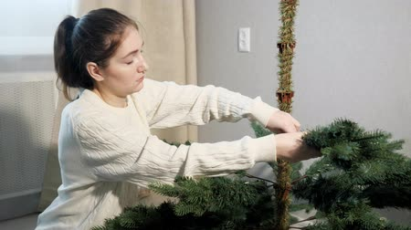 monteren : lady with dark ponytail in white sweater assembles artificial christmas tree inserting branches into trunk close view