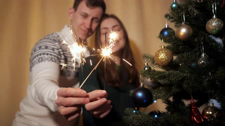 csillagszóró : happy couple in sweaters hold bright sparklers near camera and kiss standing by decorated christmas tree at home closeup