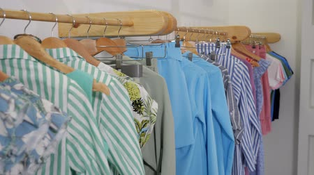 abiti appesi : camera motes along wooden hangers with fashionable colorful summer clothes on rack in modern designer shop close view