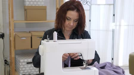 шов : Dressmaker sewing clothes. Fashion designer sewing new model of clothes. Seamstress woman works on sewing machine in tailoring workshop business. She stitches details for future clothing.