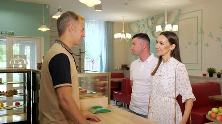 canteen : lovely couple talks with smiling bartender standing at counter in cozy decorated confectionery shop Stock Footage
