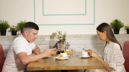 bağımlı : young man and woman use mobile phones to surf internet sitting at table with desserts and beverages in modern cafe Stok Video