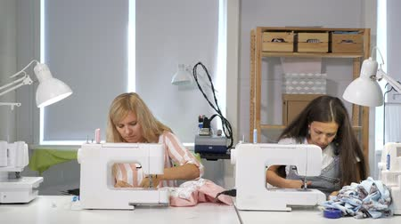 de costura : Tailoring of clothes. Seamstresses at work in workshop sewing clothes on sewing machine. Dressmakers sews clothes in atelier. Two women seamstress. Dressmaking in sewing business.