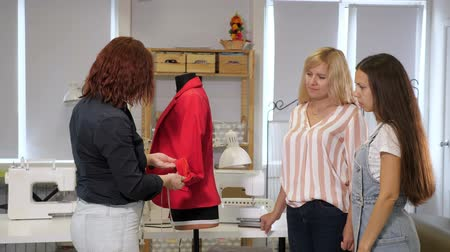 ruhakészítés : Cutting and sewing courses. Dressmaker shows women ways of sewing pockets on clothes on a mannequin. Seamster teaches her students to sew clothes show details on jacket on courses. Tailoring business. Stock mozgókép