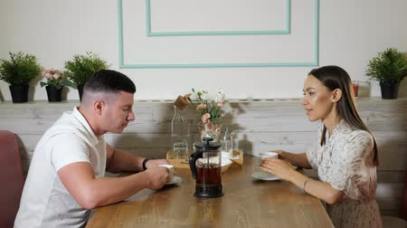 canteen : lovely young couple talk smiling and drink tea sitting at served wooden table in comfortable restaurant during date