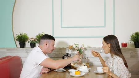 canteen : lovely young couple spends time eating delicious cakes with tea at wooden table in confectionery shop Stock Footage
