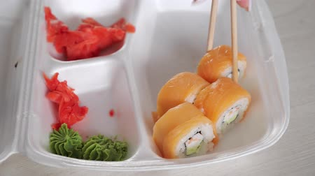 recipiente : man dips amazing philadelphia roll into soy sauce in container by wasabi and ginger with sushi chopsticks slow motion