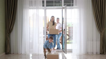domy : happy family with cute son in blue shirt enters door moving to new house holding big boxes against panoramic windows