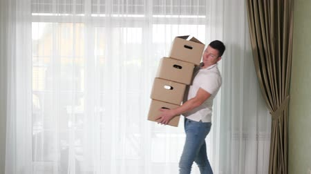вещь : strong man carries large cardboard boxes with belongings to beautiful new house with light and olive interior slow motion