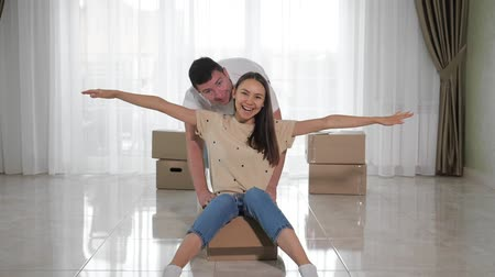relocate : strong husband rides for fun smiling wife in large cardboard box on white floor of beautiful new house slow motion