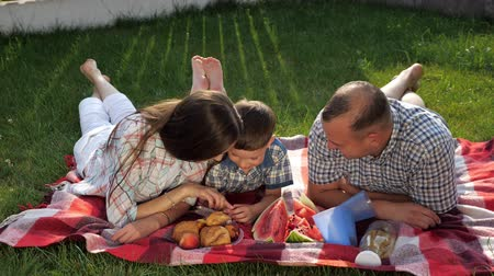 membro : happy family members lie on stomach on red blanket and enjoy picnic in green yard on summer day close view slow motion