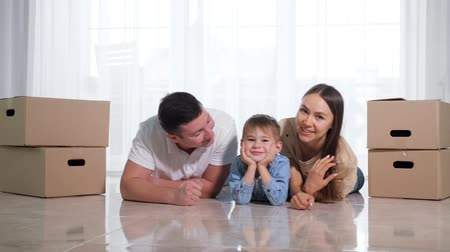 mentiras : lovely family with cute little son lies on floor in new house near beautiful wife among cardboard boxes slow motion Vídeos