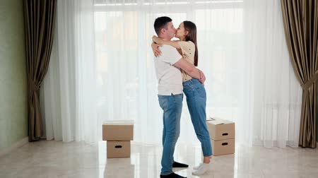 relocate : beautiful happy couple wearing blue jeans hugs and kisses standing in middle of new house lounge against big boxes Stock Footage