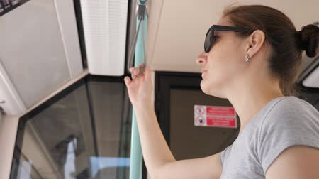 handrails : brunette woman stands in tram wagon and holds handrail bandage travelling to downtown low angle shot closeup Stock Footage