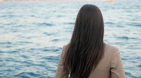 vagabundo : young unrecognizable lady with dark long hair enjoys amazing seascape standing on opposite shore on vacation backside view