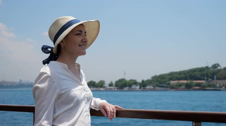 стенд : cheerful woman enjoys voyage and looks into distance standing on deck against sparkling sea under sunshine closeup