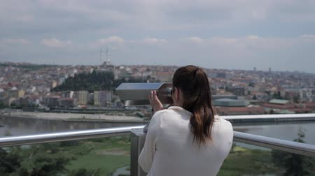 binocolo : brunette woman in white sweater looks through binoculars exploring cityscape stretching along bay backside view