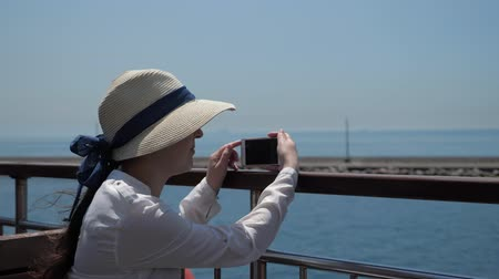 corrimão : lady in elegant straw hat sits on ship deck and makes video of beautiful seascape sailing past pier on shiny day closeup Vídeos