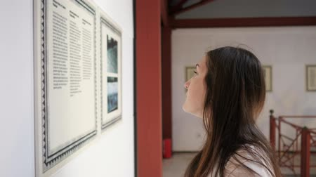 hayranlık : concentrated woman stands half face and reads information on poster in cultural Turkish museum closeup