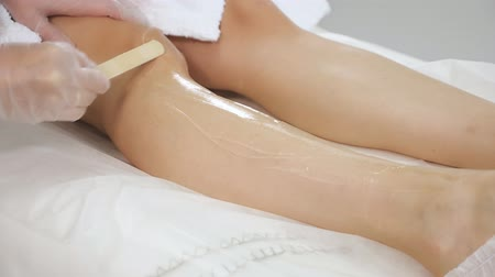 ローブ : professional woman hands spread gel on fit girl leg and knee lying on soft terry sheets in medical clinic close view