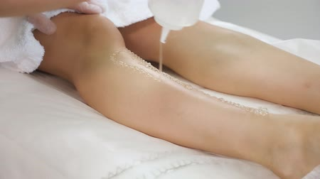 knie : woman hands in rubber gloves apply lidocaine gel on slender girl leg lying on soft sheets in medical center close view