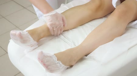 terry : beautician hands apply after laser epilation treatment on hairless leg in professional medical center close view Stock Footage