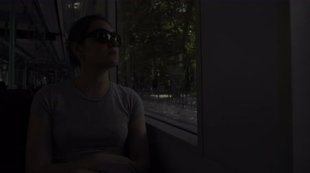 chegar : serious woman tourist in sunglasses sits at window in shady tram carriage traveling to city center for sightseeing closeup
